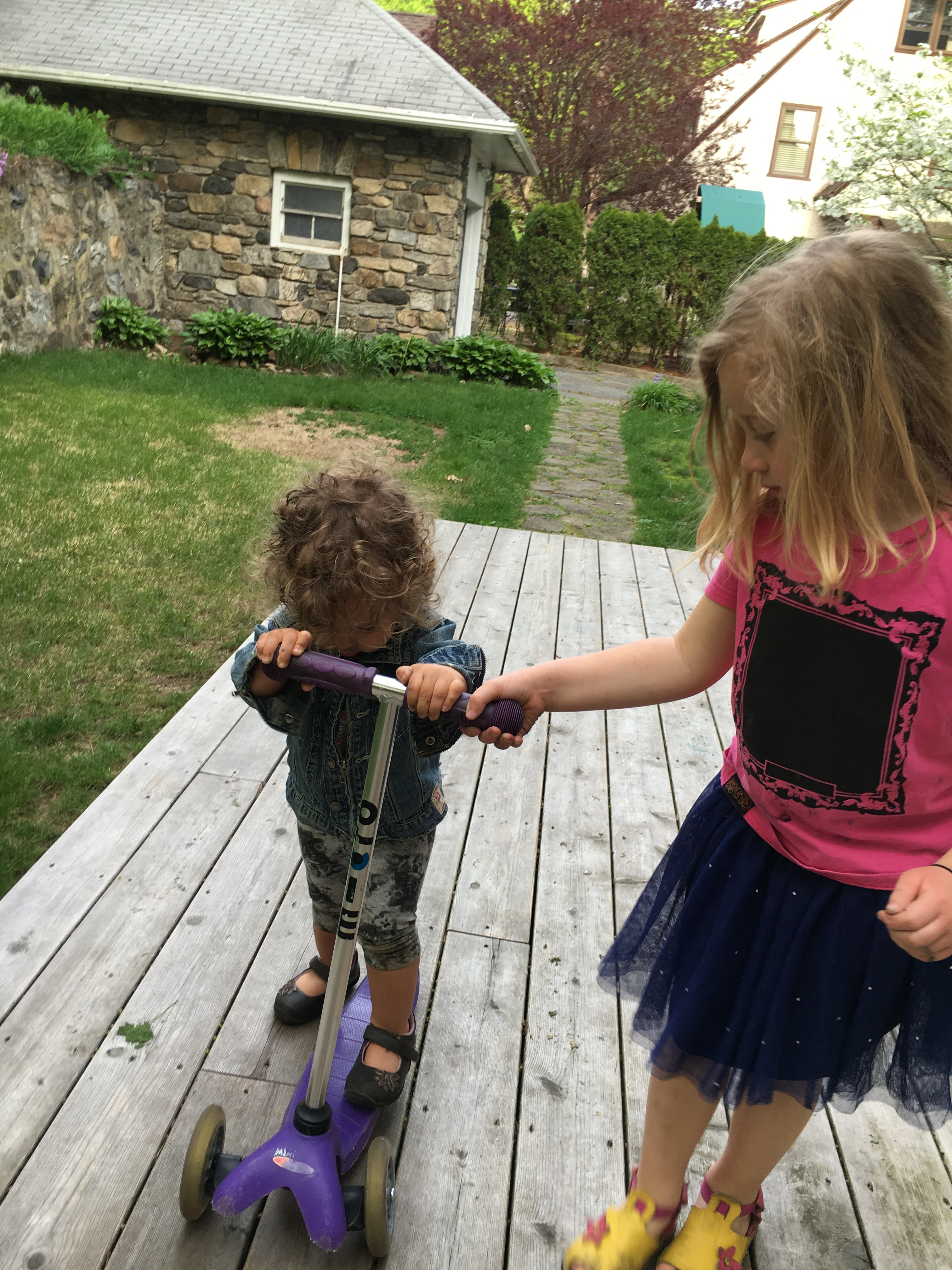 sisters playing scooters